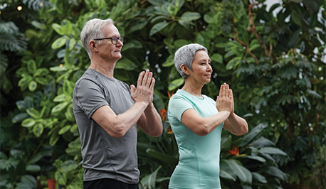 senior adults meditating outdoors