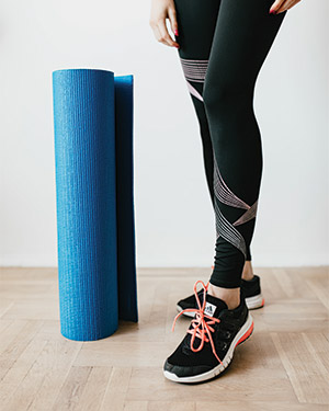 women wearing sneakers next to a rolled up yoga mat