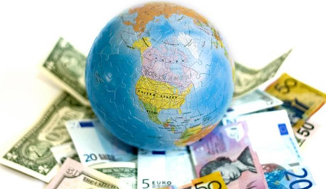 globe sitting on a pile of currency