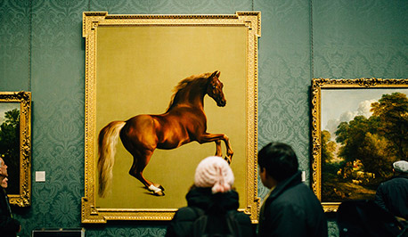 people in a museum observing a painting of a horse