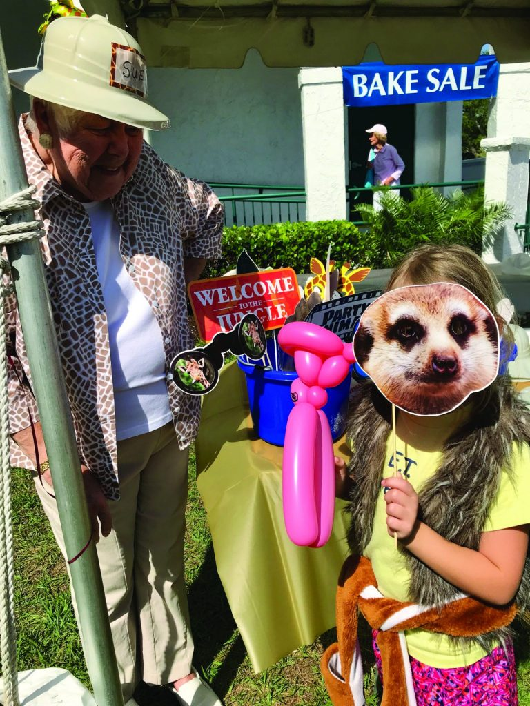 volunteer and child with balloon animal and mask
