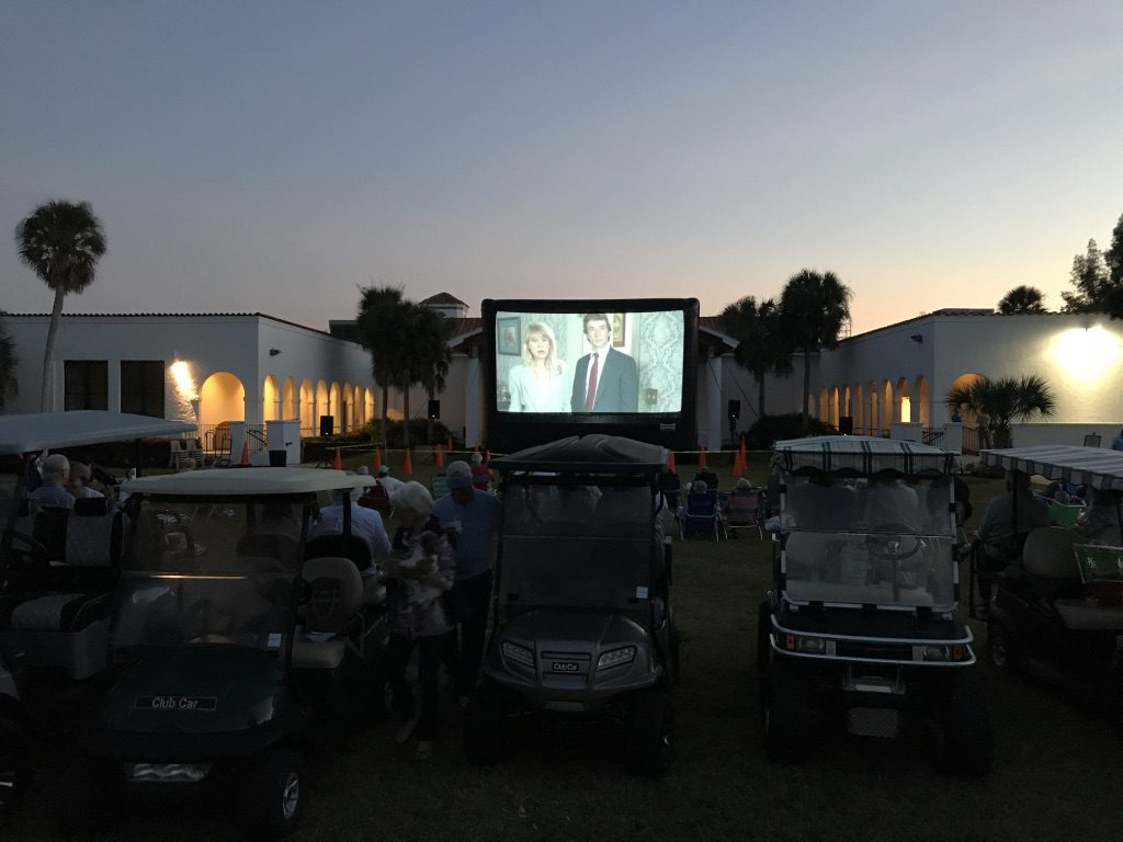 people watching a film from their golf carts
